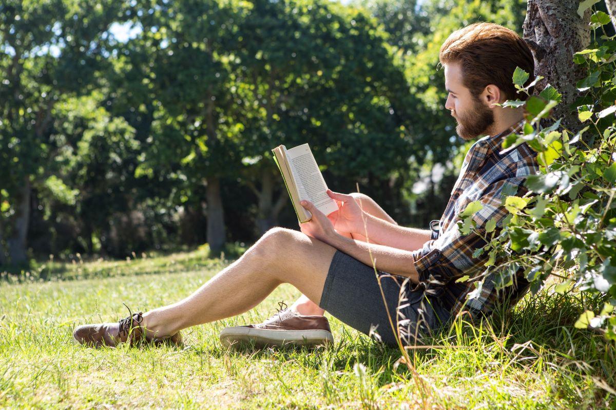 Mladík si čte knihu venku
